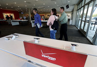 A Verizon Communications Inc. employee assist customers at a store in Orem, Utah. Sprint Nextel Corp., whose investors backed a takeover by SoftBank Corp. yesterday is now preparing to use the firepower of its soon-to-be parent company to target Verizon Wireless. Photographer: George Frey/Bloomberg