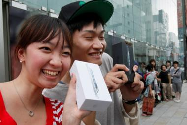 Kae Shibata, left, and Yutaro Noji show off an Apple iPhone 5 that they bought at a store in Tokyo last year. Would Japanese young people be as excited by an Apple iWatch. Apple applied for a trademark for iWatch in Japan last month, although it's not clear whether a product will be coming. Koji Sasahara/AP/File