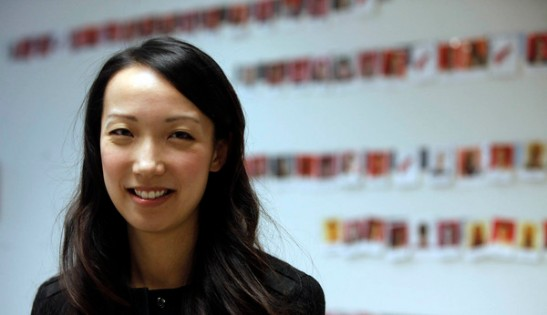Clara Shih, co-founder of Hearsay Social, a company that helps big brands reach customers on Facebook and Twitter stands in front of a wall of employee photographs at company headquarters on Monday, June 22, 2013 in San Francisco, Calif. (Karl Mondon/Bay Area News Group)