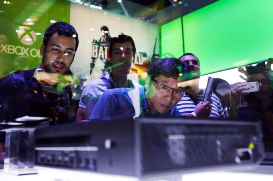 Attendees look at the Microsoft Corp. Xbox One video game console during the E3 Electronic Entertainment Expo in Los Angeles, on June 11, 2013. Photographer: Patrick Fallon/Bloomberg